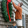 Manchester: Chuck Sullivan hangs Christmas lights with his nephew Danny Wood, 4, outside of Al's Cafe on Central Street Wednesday afternoon. Mary Muckenhoupt/Gloucester Daily Times
