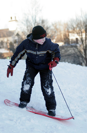 Essex: Reilly Zubricki, 12, snowboards down the hill behind Town Hall in Essex. Photo by Kate Glass/Gloucester Daily Times