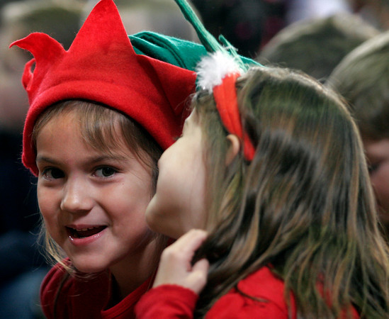 """Gloucester: Beeman Elementary School kindergarteners Rhuana Ramirez, left, and Ellie Sutera, right, giggle while singing """"Jingle Bells"""" during the school's holiday concert yesterday afternoon. Photo by Kate Glass/Gloucester Daily Times Wednesday, December 16, 2009"""