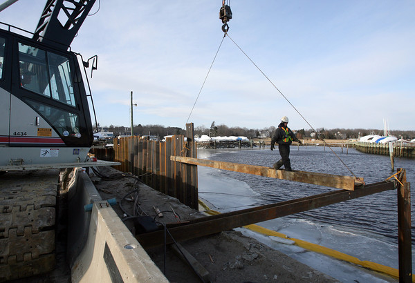 Essex: Sean White of Atlantic Support Installation walks across a steel beam as they build a dam along the Causeway to catch debris from the construction project. Photo by Kate Glass/Gloucester Daily Times