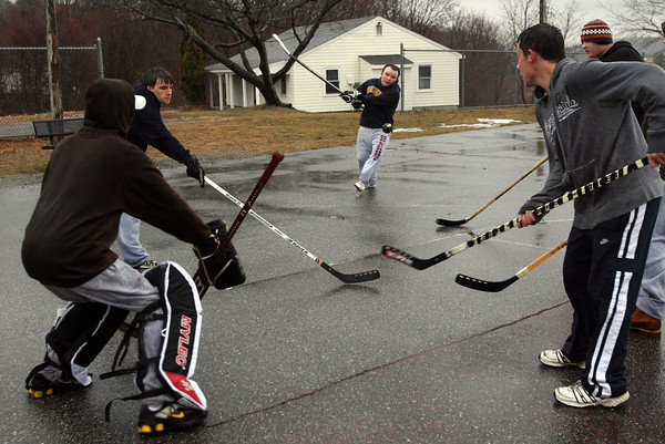 Gloucester: Dan Enos shoots the ball through Gilbert Oliver, Brian Enos, Matt Muniz-Silva, and Alex Natti while playing street hockey in the rain at Stage Fort Park yesterday afternoon. Photo by Kate Glass/Gloucester Daily Times