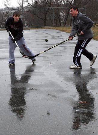 Gloucester: Brian Enos and Matt Muniz-Silva play street hockey in the rain at Stage Fort Park yesterday afternoon. Photo by Kate Glass/Gloucester Daily Times