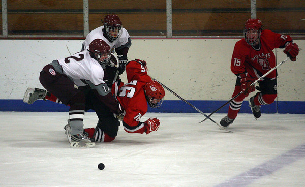 Gloucester: Rockport's Scott Greene and Matt Ledbury knock Amesbury's Aaron Sanford off his skates as Jacob Burns looks on at the Talbot Rink yesterday. Photo by Kate Glass/Gloucester Daily Times