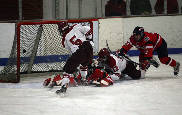 Gloucester: Gloucester's Geoff Kennedy knocks the puck past Saugus goalie Nick Hegarty as Gloucester's Alex Webb and Saugus' AJ Guthro slide in during the Fishermen's home opener last night. Photo by Kate Glass/Gloucester Daily Times Wednesday, December 16, 2009