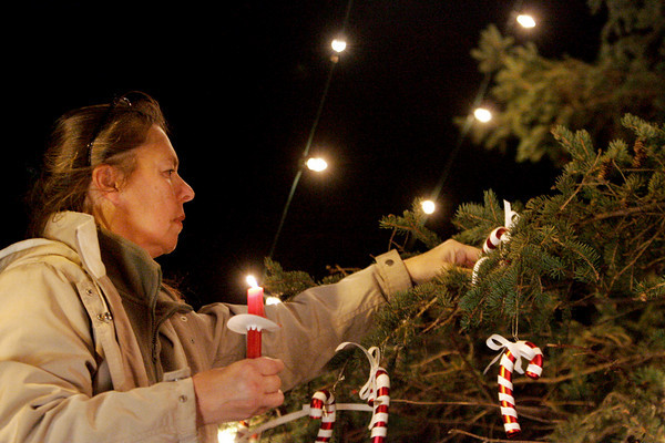 Essex: Marilyn Klypka-Simpson hangs an ornament at the lighting of the Memory Tree in front of Essex Town Hall Thursday evening.  The memory tree allows people to hang ornaments for loved ones who have passed away. Mary Muckenhoupt/Gloucester Daily Times