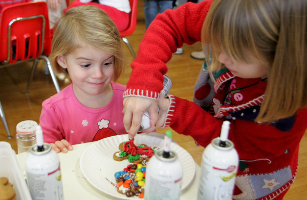 Essex: Megan Hurd, 3, looks pleasantly surprised at how much frosting her sister Althea, 6, was adding to her gingerbread cookie during Breakfast with Santa at Essex Elementary School Saturday morning. Mary Muckenhoupt/Gloucester Daily Times