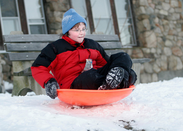 Essex: Lily Schrafft, 11, sleds down the hill behind Town Hall in Essex. Lily did not go near the section with the jump though, because she didn't want to get herself killed. Photo by Kate Glass/Gloucester Daily Times