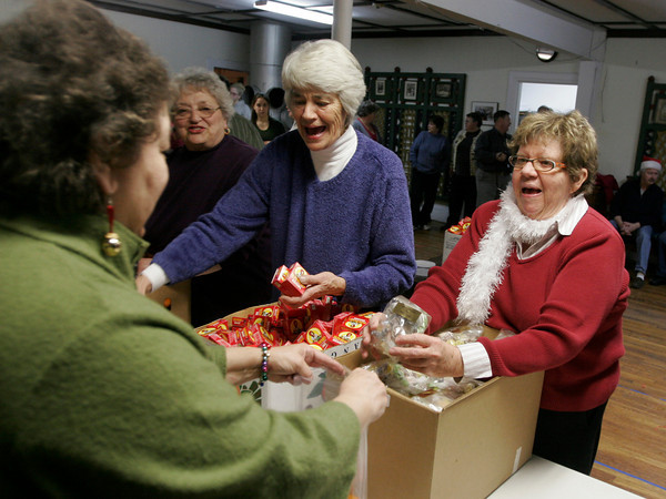 Rockport: Susan Morris and Carole Findley hand out raisins and candy to be put in baskets that delivered to elderly shut ins on Christmas morning. Approximately 50 members and friends of the Rockport Christmas Tree Committee gathered at Spiran Hall Tuesday night to help prepare for the event, which is funded through donations. The volunteers also prepared over 500 bags for Santa to hand out to children at Dock Square on Christmas morning. Donations may be mailed to the Rockport Christmas Tree Committee, c/o/ Doreen Carter, 2 Mary Helen Way, Rockport, MA 01966, or dropped off at any Rockport National Bank location or Smith Lumber and Hardware. Photo by Kate Glass/Gloucester Daily Times