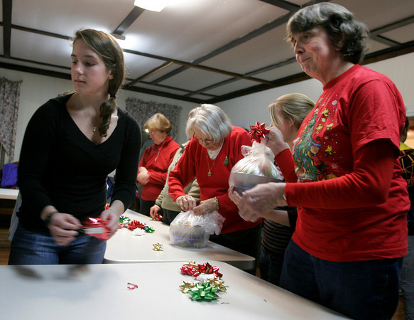 Rockport: Emma Littlefield and Nancy Mears help wrap 550 bowls filled with goodies that will be delivered to elderly shut ins on Christmas morning. Approximately 50 members and friends of the Rockport Christmas Tree Committee gathered at Spiran Hall Tuesday night to help prepare for the event, which is funded through donations. The volunteers also prepared over 500 bags for Santa to hand out to children at Dock Square on Christmas morning. Donations may be mailed to the Rockport Christmas Tree Committee, c/o/ Doreen Carter, 2 Mary Helen Way, Rockport, MA 01966, or dropped off at any Rockport National Bank location or Smith Lumber and Hardware. Photo by Kate Glass/Gloucester Daily Times