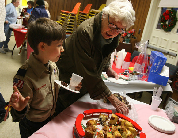 """Manchester: J.P. Rouillard of Cub Scout Pack 30 points out the good cookies to Jean Peloquin after singing Christmas Carols at The Pines yesterday afternoon. """"The boys really tried hard and they sounded good,"""" Peloquin said. The scouts also brought gifts for the seniors. Photo by Kate Glass/Gloucester Daily Times Wednesday, December 16, 2009"""