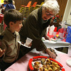 "Manchester: J.P. Rouillard of Cub Scout Pack 30 points out the good cookies to Jean Peloquin after singing Christmas Carols at The Pines yesterday afternoon. ""The boys really tried hard and they sounded good,"" Peloquin said. The scouts also brought gifts for the seniors. Photo by Kate Glass/Gloucester Daily Times Wednesday, December 16, 2009"