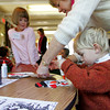 "Gloucester: Matthew McDougal, 3, works on his snowman with some help from his grandmother, Jennifer, at the Eastern Point Day School Thursday morning.  After listening to the story ""Frosty the Snowman"" the kidergarteers helped bring frosty to life by amking their own snowman puppets. Mary Muckenhoupt/Gloucester Daily Times"