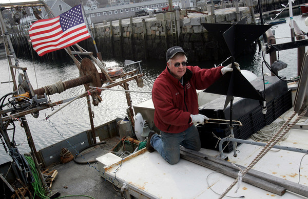 Rockport: Captain Bill Lee removes the symbol required by rule 26 of international fishing regulations from his boat, the Ocean Reporter, after selling his fishing permit after working for 36 years as a commercial fisherman. Photo by Kate Glass/Gloucester Daily Times Tuesday, December 7, 2009