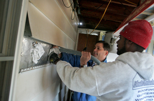 Gloucester: Sen. Bruce Tarr helps Deivis Nunez of Atlantic Weatherization install insulation to weatherize the home of Mary Muise on Linnett Place in Gloucester Friday afternoon.  As part of the Energy Bucks initiative Sen. Bruce Tarr, Action Inc., and other local leaders came together to weatehrize this home to promote Energy Efficiency and raise awareness of the cost-saving energy programs.  Mary Muckenhoupt/Gloucester Daily Times