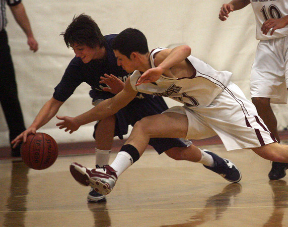 Gloucester: Rockport's Kevin Corrigan and Hamilton-Wenham's Jake Prince dive for the ball during the championship game of the 4th Annual BankGloucester Holiday Tournament last night. Photo by Kate Glass/Gloucester Daily Times