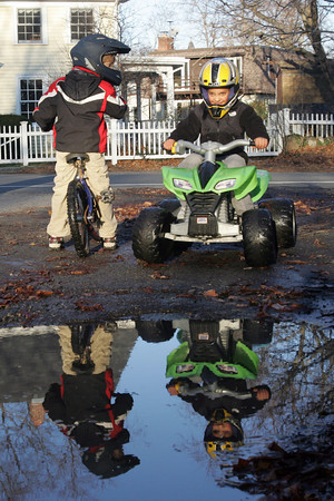 Rockport: Trey Rochford, 7, left, and Kaidin Rapp 6, take turns riding through a puddle at the end of their driveway yesterday afternoon. Photo by Kate Glass/Gloucester Daily Times Tuesday, December 1, 2009