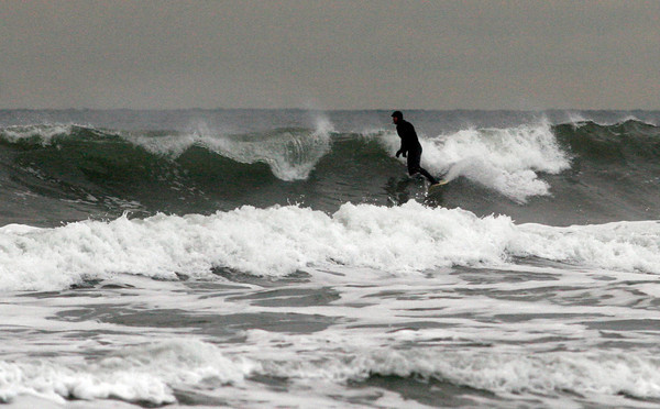 Gloucester: A surfer catches a wave off Good Harbor Beach on Monday afternoon. Photo by Kate Glass/Gloucester Daily Times