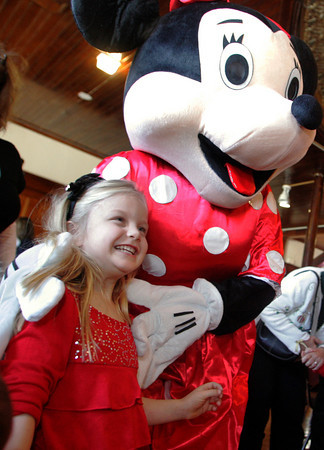 Gloucester: Kendra Brown, 4, happily poses with Mini Mouse at the Docksiders Benefit Concert held at City Hall Saturday morning. The Docksiders have traveled to Walt Disney resorts three times in the past five years, but on Saturday, they brought the Disney characters to Gloucester for a benefit breakfast to help raise money for their upcomming trip to Hawaii.  Mary Muckenhoupt/Gloucester Daily Times