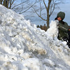 Manchester: Charlie Stinsmuehlen tries to build a large snowball from a pile of snow at the Brook Street Playground after school on Monday. Photo by Kate Glass/Gloucester Daily Times