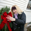 Gloucester: Krista Haley attaches a red bow to the fesitve greens surrounding her mailbox as she decorates for Christmas in front of her South Street home on Mt. Pleasant Street Saturday afternoon. Mary Muckenhoupt/Gloucester Daily Times