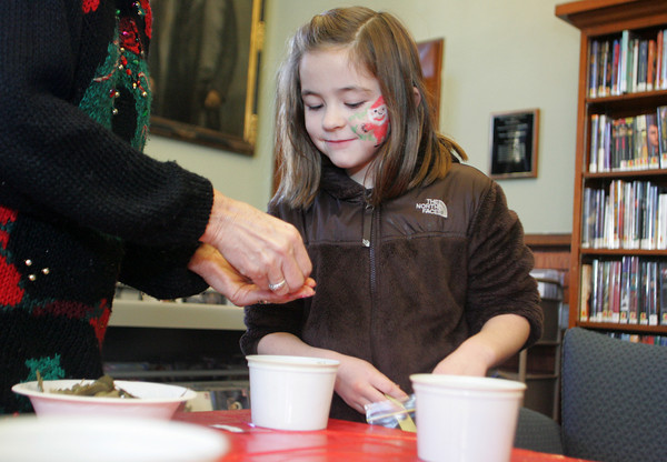 Manchester: Sophia Pomeroy, 8, looks at the shapes of the star anise as Pat Martines helps her make a bag of pot-pourri at the Manchester Public Library Saturday.  Along with star anise there were many other things to choose for a pot-pourri bag including cloves, orange peel and bay leafs as well as scented oil to be added at the end. Mary Muckenhoupt/Gloucester Daily Times