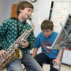 Essex: Forth Grader Chris Brosch practices the saxaphone as his friend Duncan Bissonnette keeps an eye on his sheet music to make sure Chris is playing the right notes during a music lesson with Richard Carpenter at Essex Elementary School Friday. Mary Muckenhoupt/Gloucester Daily Times