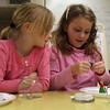 Essex: Zoe Corwin watches as Alanna Fitzgerald sculpts clay to hold her figurine in place as they make snow globes at Essex Elementary School on Wednesday. The after school program was put together by the Essex Youth Commission. Photo by Kate Glass/Gloucester Daily Times