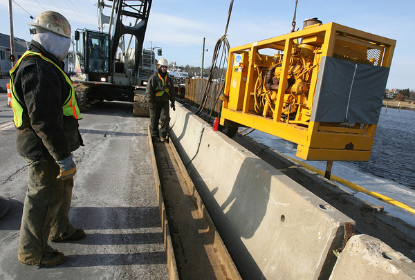 Essex: Bill Gyman and Sean White of Atlantic Support Installation guide a hydraulic generator down the Causeway yesterday. The machinery powers the pile driver used to place steel sheets for a temporary dam. Photo by Kate Glass/Gloucester Daily Times
