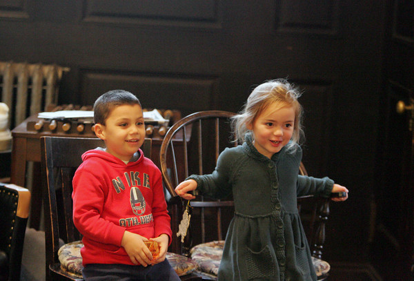 """Manchester: Marco Bussone, 4, and his good friend Annabel Smith, 5, listen to librarian Sarah Collins read """"Dream Snow"""" by Eric Carle during a special holiday story time at the Manchester Public Library Saturday afternoon.  Mary Muckenhoupt/Gloucester Daily Times"""