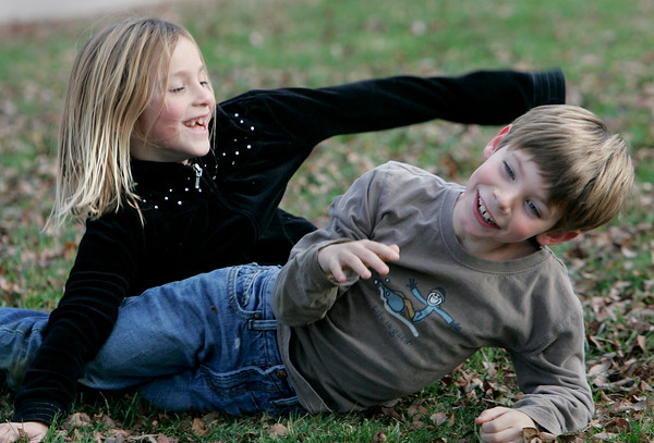 Gloucester: Callie MacLaughlin, 7, tackles her friend John Andrew, 7, while playing at their bus stop in front of Annisquam Village Church Wednesday afternoon. Mary Muckenhoupt/Gloucester Daily Times
