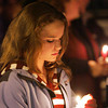 "Essex: Samantha Woodman, 12, looks down at her candle as the North Shore Bell Ringers play ""Silent Night"" at the lighting of the Memory Tree in front of Town Hall Thursday evening.  The memory tree allows people to hang ornaments for loved ones who have passed away. Mary Muckenhoupt/Gloucester Daily Times"