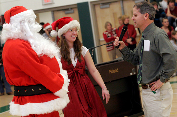 Manchester: Paul Murphy interviews Mr. and Mrs. Claus, played by Tim Surette and Emily Malik, during the holiday assembly at Manchester Essex Regional High and Middle School on Wednesday. The two said they've been very busy making toys and baking cookies. Photo by Kate Glass/Gloucester Daily Times