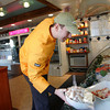 Gloucester: Michael Sawyers puts a bowl of sea scallops in the the dislay case of Intershell, a fish market located on Commercial Street which will hold it's grand opening today. Mary Muckenhoupt/Gloucester Daily Times