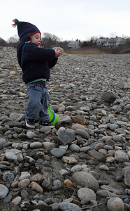 Rockport: Tyler Burke, 2, of Essex smiles as he finds a rock suitable for painting while walking with his family at Cape Hedge in Rockport yesterday afternoon. Tyler and his brother, Connor, got paints for Christmas and were collecting a bucket full of rocks to paint. Photo by Kate Glass/Gloucester Daily Times