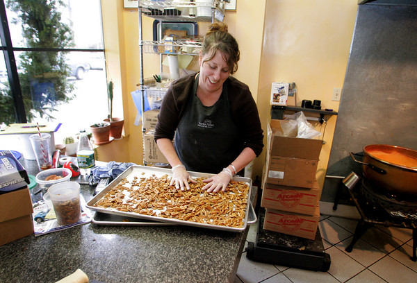 Gloucester: Hallie Baker, owner of Turtle Alley Chocolates, lays out a pan on pecans that will become turtles in her shop Monday afternoon.  Baker's chocolate business has drawn interest from Food Network, Gourmet magazine, Road Food etc. Mary Muckenhoupt/Gloucester Daily Times