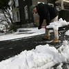 Gloucester: George Roark shovels snow away from the drains along Beauport Ave in Gloucester yesterday morning. Photo by Kate Glass/Gloucester Daily Times