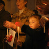 Gloucester: Elizabeth Dinan and her grandmother, Carole Horne, light candles in memory of Elizabeth's father, Joseph Dinan, during the lighting of the Hospice of the North Shore Tree of Lights at BankGloucester last night. Dozens of people attended the event. Photo by Kate Glass/Gloucester Daily Times
