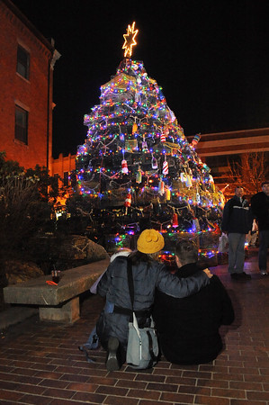 Marc and Margaret Chadbourne from Rockport sit with their children Henry 3, and Cecilia 1, as they look at the lights on Lobster Trap Tree Saturday night on Main St. Desi Smith/Gloucester Daily Times. December 11,2010.