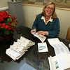 Gloucester: Mayor Carolyn Kirk tries to catch up on writing several hundred holiday cards during her first day back at City Hall yesterday. The mayor had been sick for two weeks. Photo by Kate Glass/Gloucester Daily Times