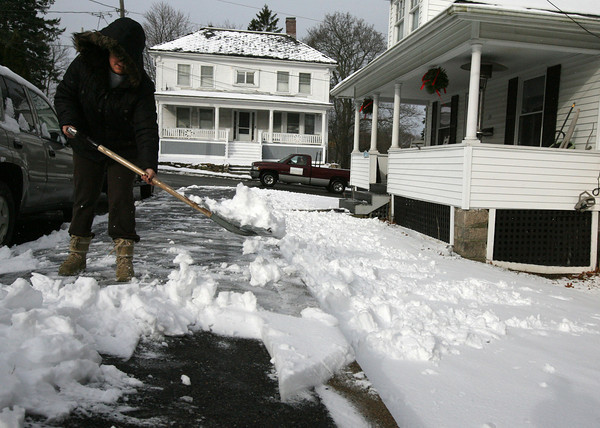 Gloucester: Christina Collins shovels snow from the sidewalk along Beauport Ave. in Gloucester on Thursday. More snow is forecast for Sunday. Photo by Kate Glass/Gloucester Daily Times
