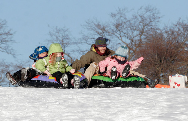 Gloucester: Amy Barry holds onto Mila Barry, Madelyn Christensen, and Willow Barry to form a train as they go sledding at Stage Fort Park. Photo by Kate Glass/Gloucester Daily Times