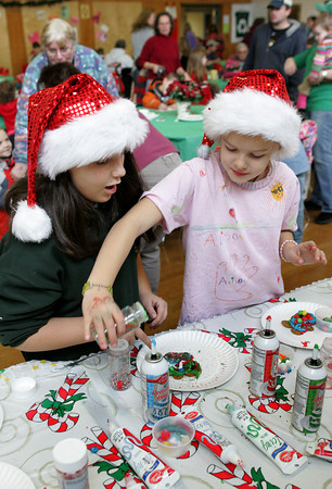 Essex: Emma DiZio, 9, left, and her friend Ali Reed, 9, try and see how much frosting they can fit on their gingerbread cookies during breakfast with Santa at Essex Elementary School Saturday monring. Mary Muckenhoupt/Gloucester Daily Times