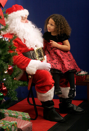 """Gloucester: Samara Salah, 4, tells Santa what she would like him to bring for Christmas during a taping of """"Santa Party!"""" at the Cape Ann TV Studio. """"Santa Party!"""" will air from 5:30 to 9:30 p.m. on Christmas Eve and from 6 a.m. to 1 p.m. and 5:30 to 9:00 p.m. on Christmas Day. Photo by Kate Glass/Gloucester Daily Times"""