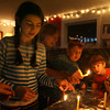 Gloucester: Rebecca Dowd, Gretchen Putnam, Ari Dimond-Putnam, and Treely Dowd each light the first candle of different menorahs as they celebrate the first night of Hanukkah last night. Photo by Kate Glass/Gloucester Daily Times