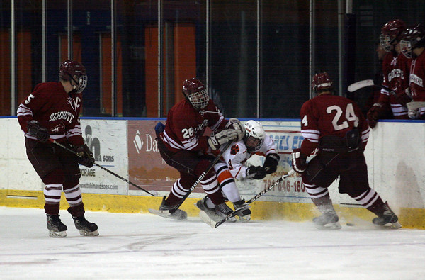 Salem: Gloucester's Sal Taormina shoves Beverly's Kevin Lally into the boards as his teammates, Geoff Kennedy, and Coltyn Rivas look on during their season opener at Rockett Arena last night. The Fishermen lost 3-2. Photo by Kate Glass/Gloucester Daily Times