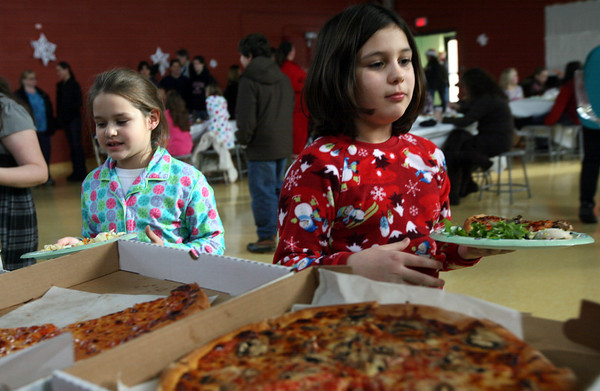 Gloucester: Lucia Dimeo, right, and Sarah Bradshaw look over the selection of pizza at the Gloucester Community Arts Charter School during a party to celebrate the holidays and the school's green light to go forward. Photo by Kate Glass/Gloucester Daily Times