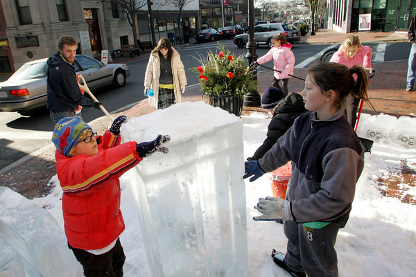 Gloucester: Kids, icluding Henry Jacques, front left, and Taylor Lombardo, front rght, work at building a structure with blocks of ice donated by Cape Pond Ice in front of Cape Ann Art Haven Saturday morning. David Brooks, pictured back left, of Art Haven helped move the ice and organize the building as different kids came by all day long to help. Mary Muckenhoupt/Gloucester Daily Times