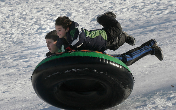 Gloucester: Alex Ciolino, right, nearly flies off a snowtube as he and Nicholas Curcuru go sledding near Boudreau Field yesterday afternoon. Photo by Kate Glass/Gloucester Daily Times