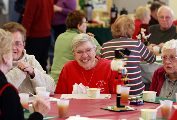 Manchester: Genevieve Pietrowski of Manchester laughs with her friends while attending the Senior Citizen Holiday Luncheon at the Manchester Essex Regional High School Saturday. The luncheon was sponsored by the school's student body and included performances by the high school band and chorus. Mary Muckenhoupt/Gloucester Daily Times