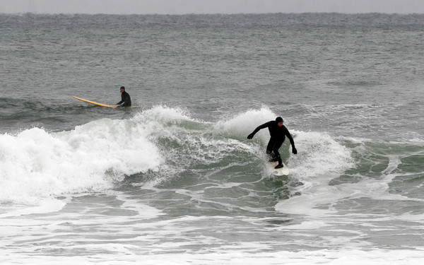 Gloucester: Two surfers take advantage of the slow rolling waves off the back shore yesterday. Photo by Kate Glass/Gloucester Daily Times